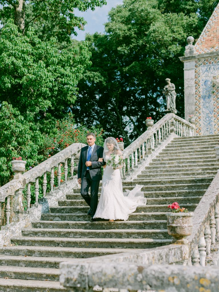 Bride and father walking down staircase at Marquês de Fronteira Palace by Portugal Wedding Photographer