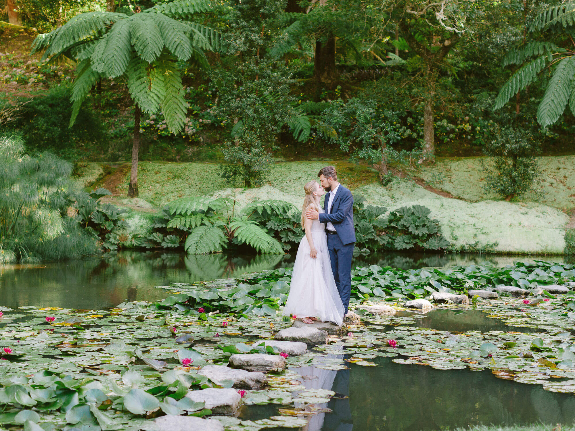 Bride and groom in the centre of a lake with water lilies on the wedding day in the Azores by Portugal Wedding Photographers