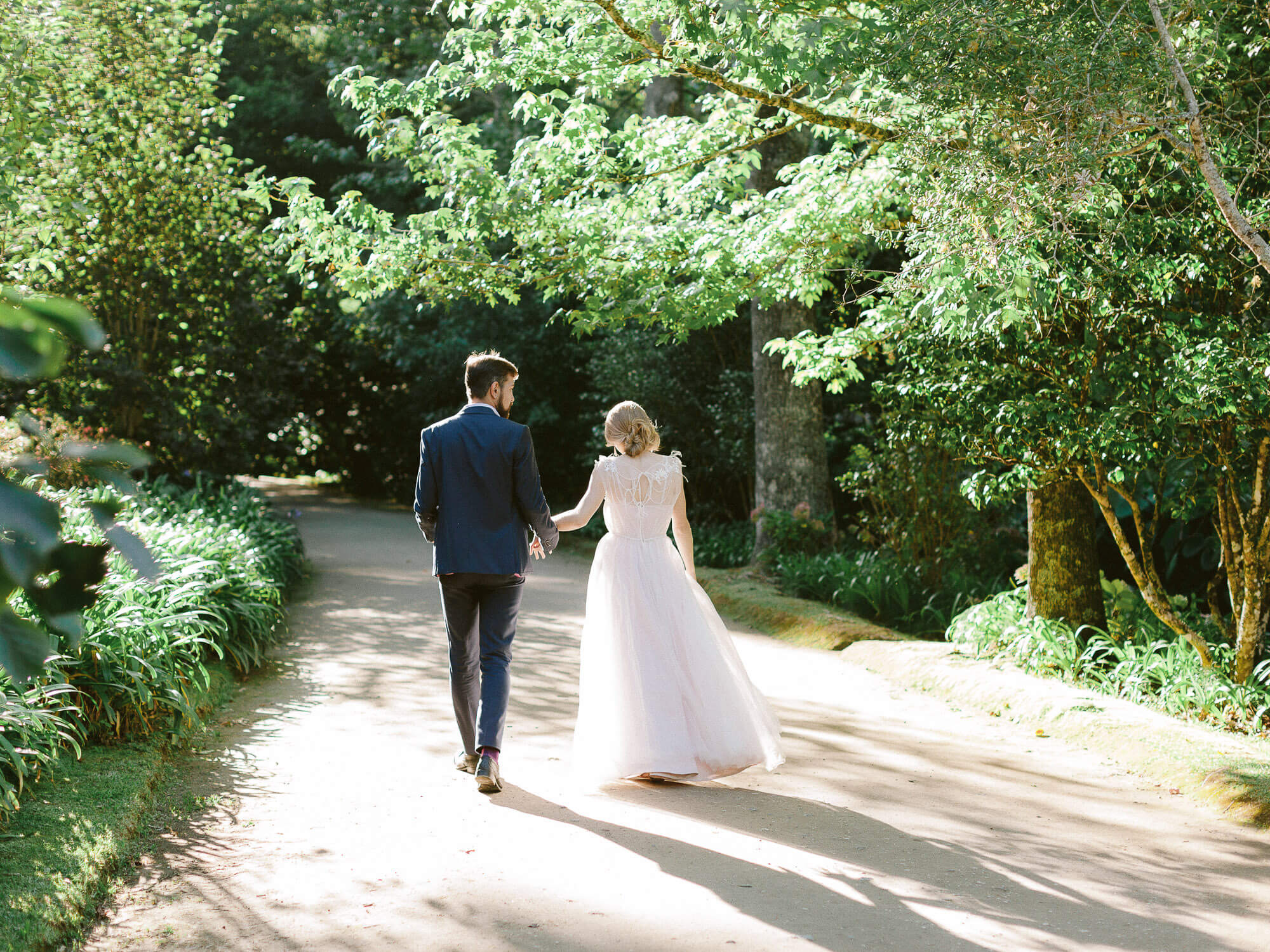 Wedding couple walking along beautiful park in the Azores on their wedding day by Portugal Wedding Photography