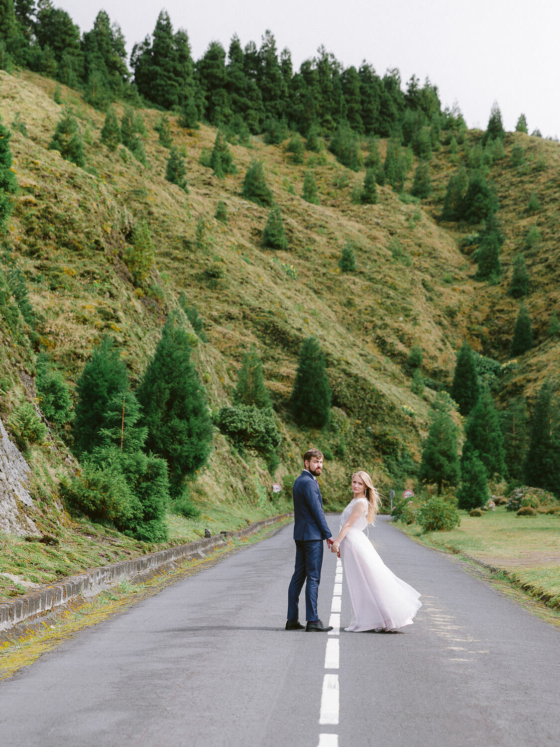 bride and groom on an empty road with typical Azores landscape on their wedding day by Portugal Wedding Photographers