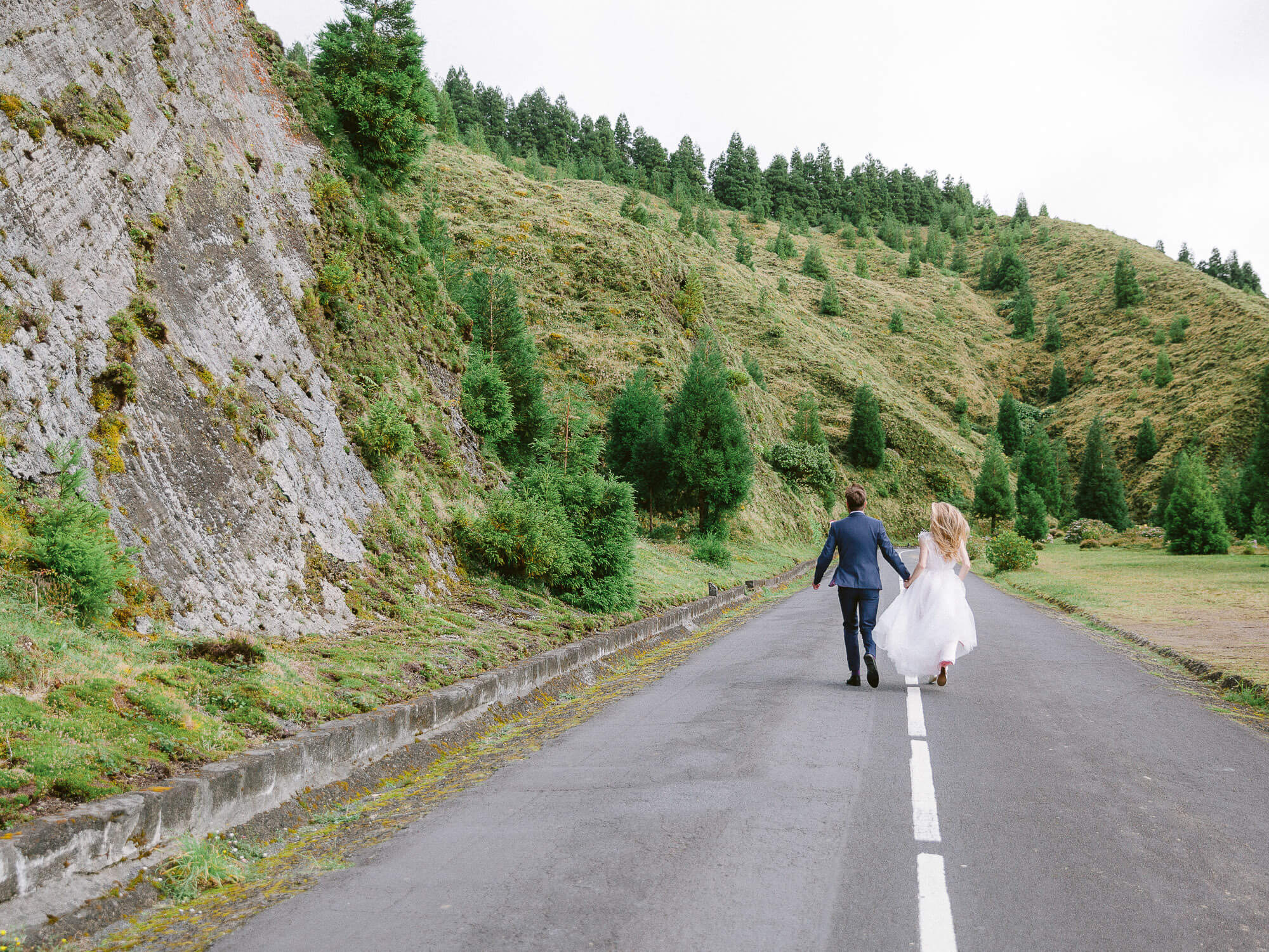 Bride and Groom happily running on empty road in Azores on their Destination Wedding by Portugal Wedding Photographer