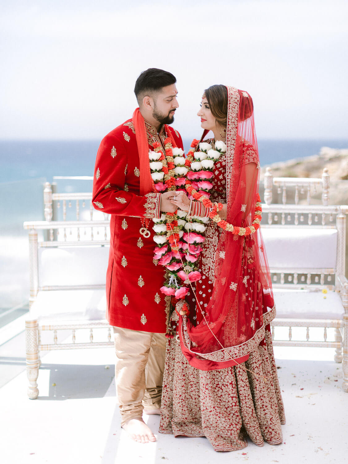 hindu wedding couple with red and golden ornamented vests by Portugal Wedding Photographer
