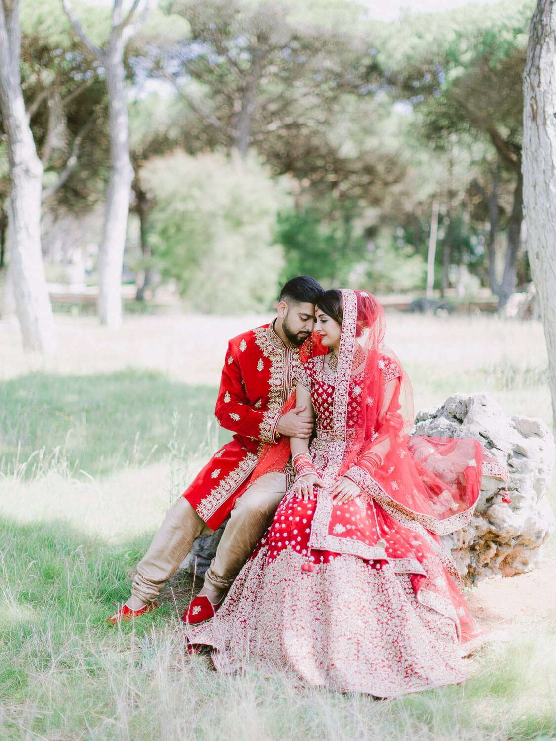 beautiful Hindu wedding couple seated portrait on a park with gorgeous Hindu gowns by Portugal Wedding Photographer