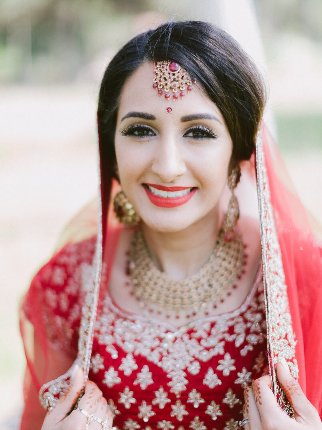 Happy Hindu bride on the wedding day with amazing Hindu gown and jewellery by Portugal Wedding Photographer