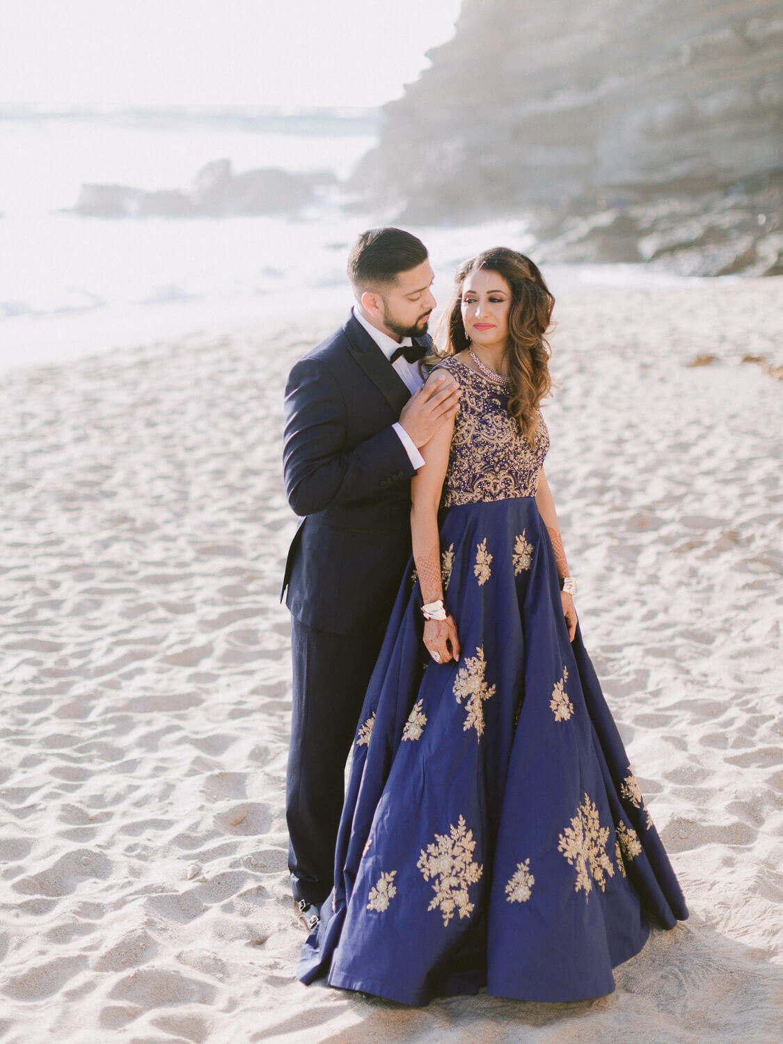 Hindu bride and groom in formal attires portrait at the beach by Portugal Wedding Photographer