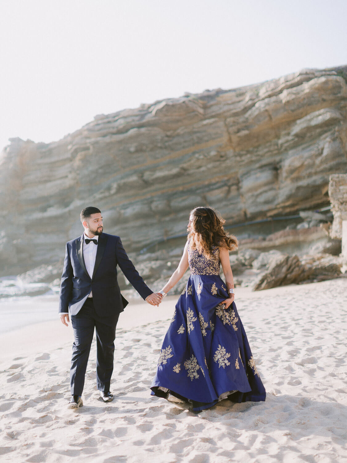 Hindu bride and groom romantic stroll at the beach by Portugal Wedding Photographer