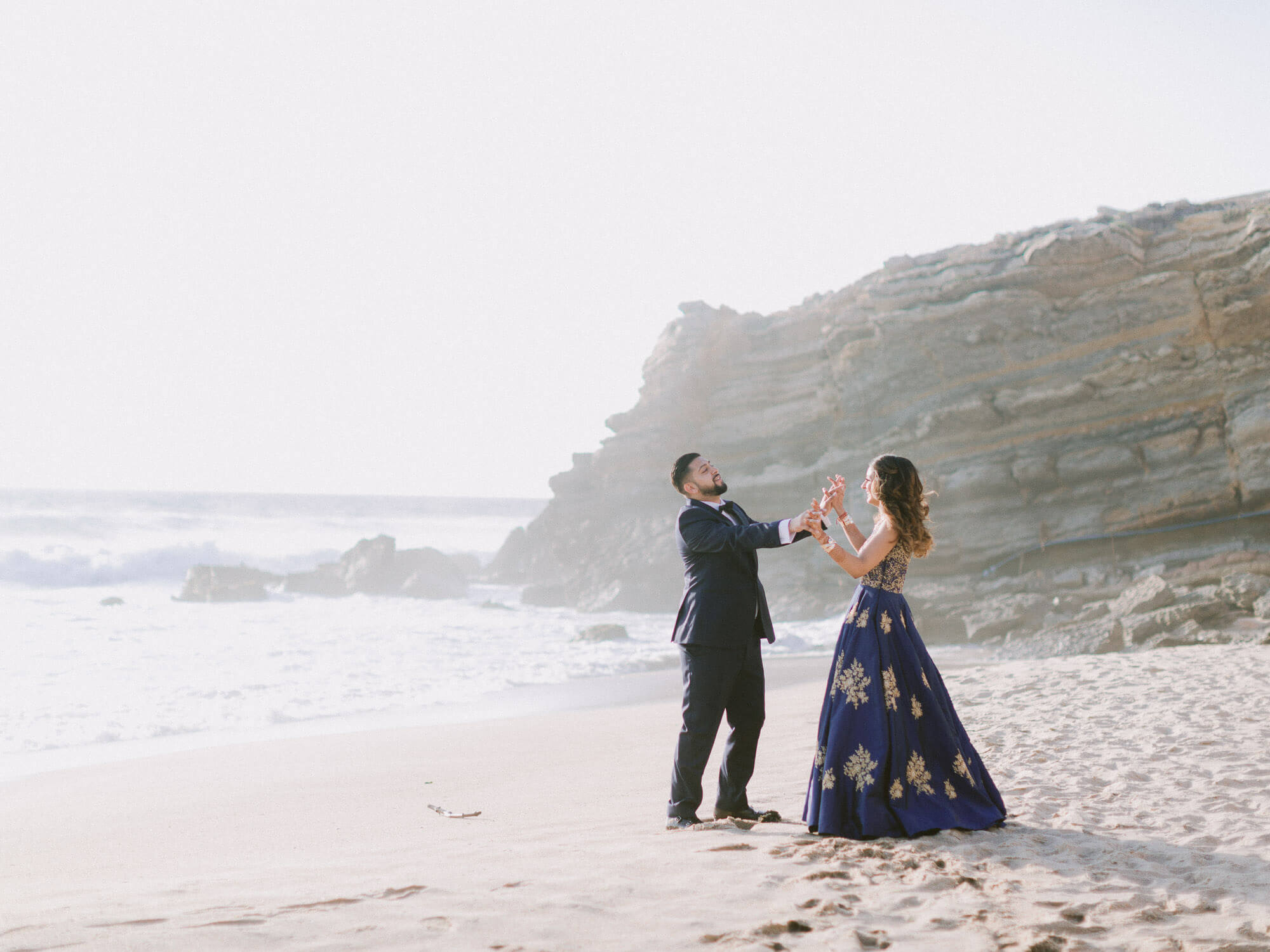 Joyful Hindu bride and groom romantic pose at the beach by Portugal Wedding Photographer