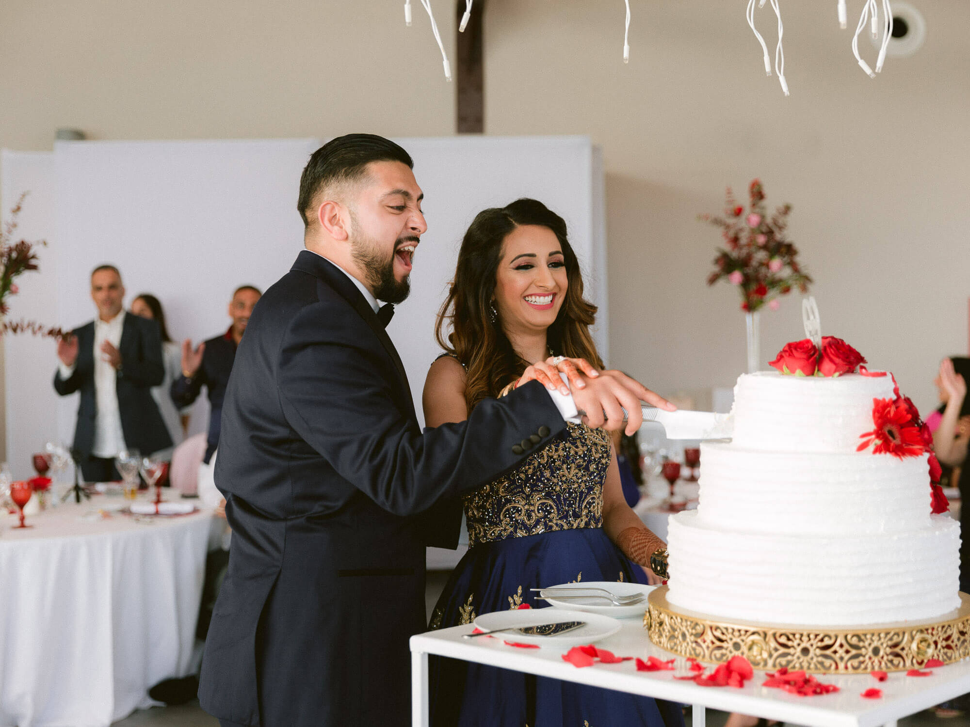 Hindu couple happily cutting wedding cake by Portugal Wedding Photographer