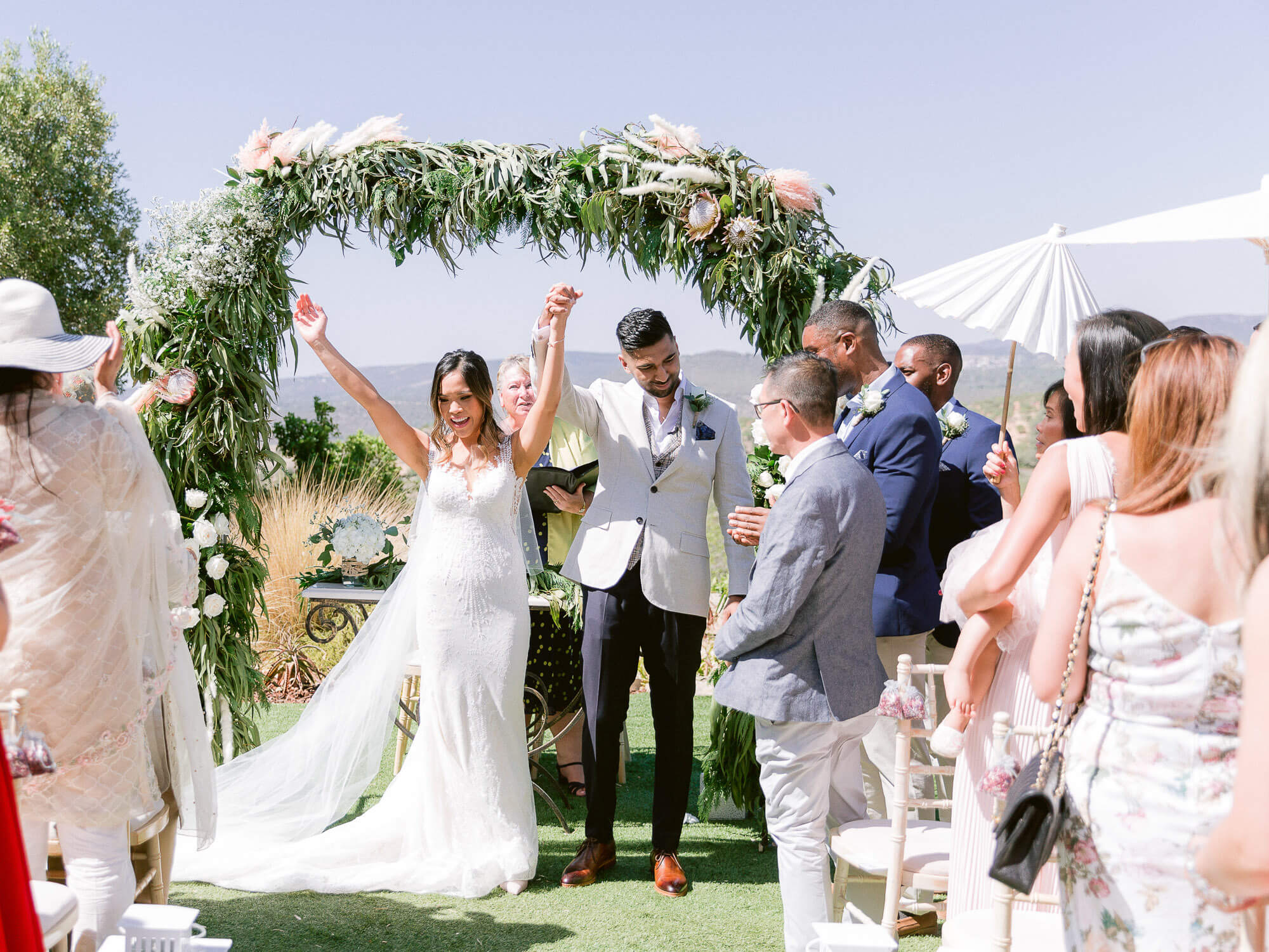 bride and groom cheering at the end of a wedding ceremony in the Algarve by Portugal Wedding Photographer