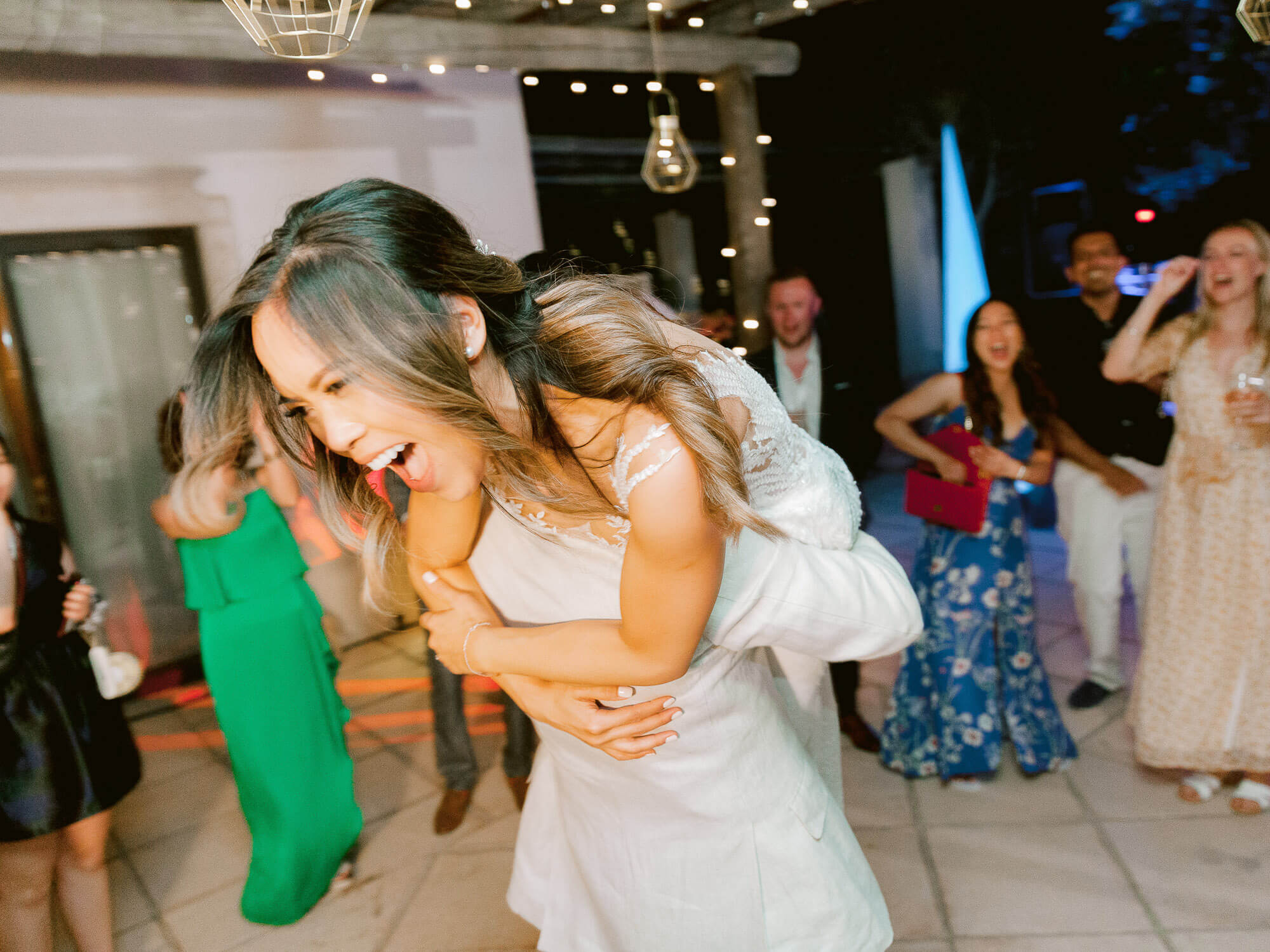the bride being held up during the party at a destination wedding in the Algarve by Portugal Wedding Photographer