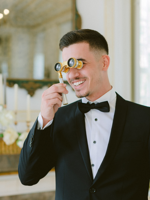 playful, elegant groom with opera binoculars at Palacio de Queluz, Lisbon by Portugal Wedding Photographers