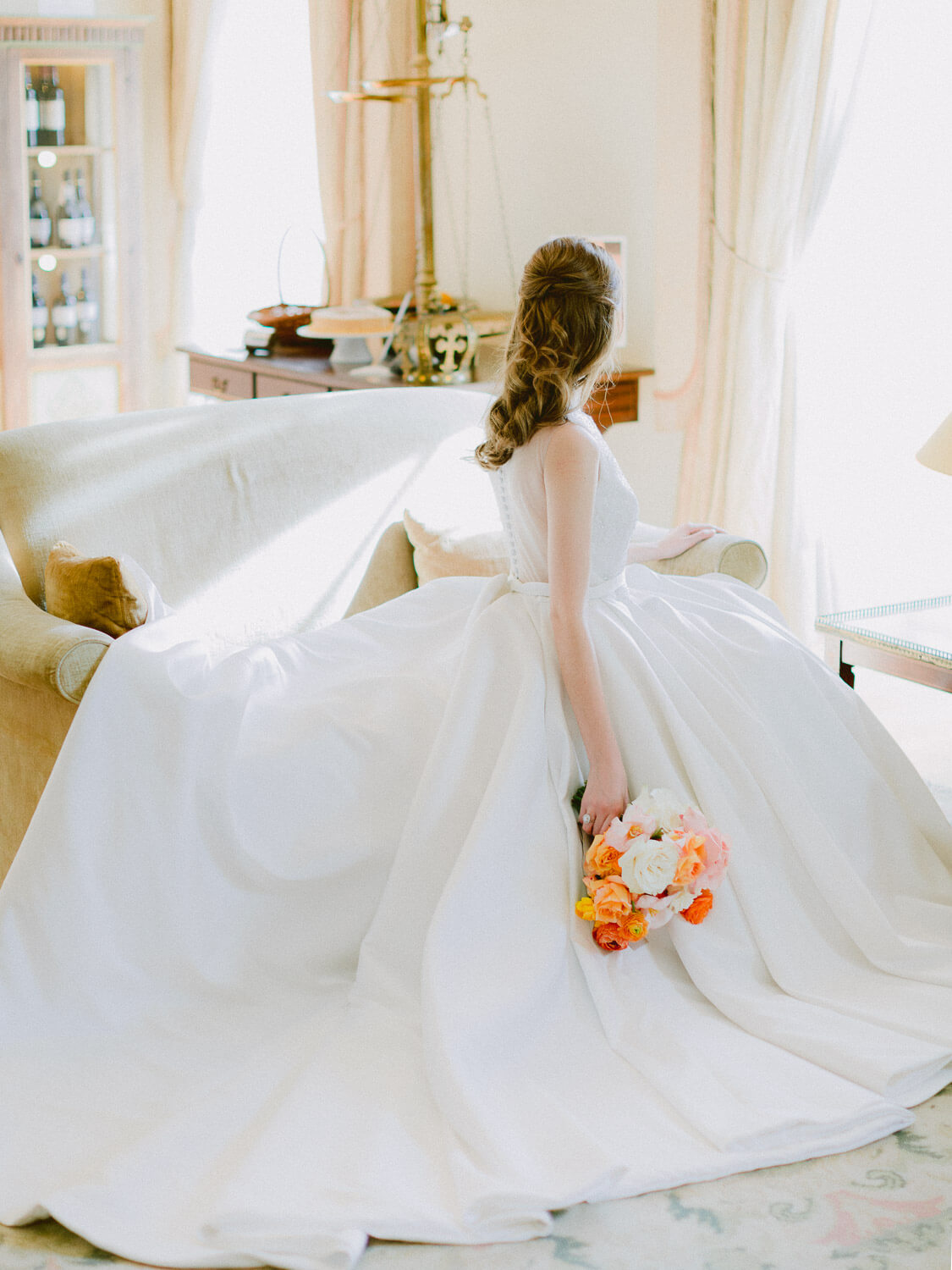seating bride holding a colourful bouquet by Portugal Wedding Photographer