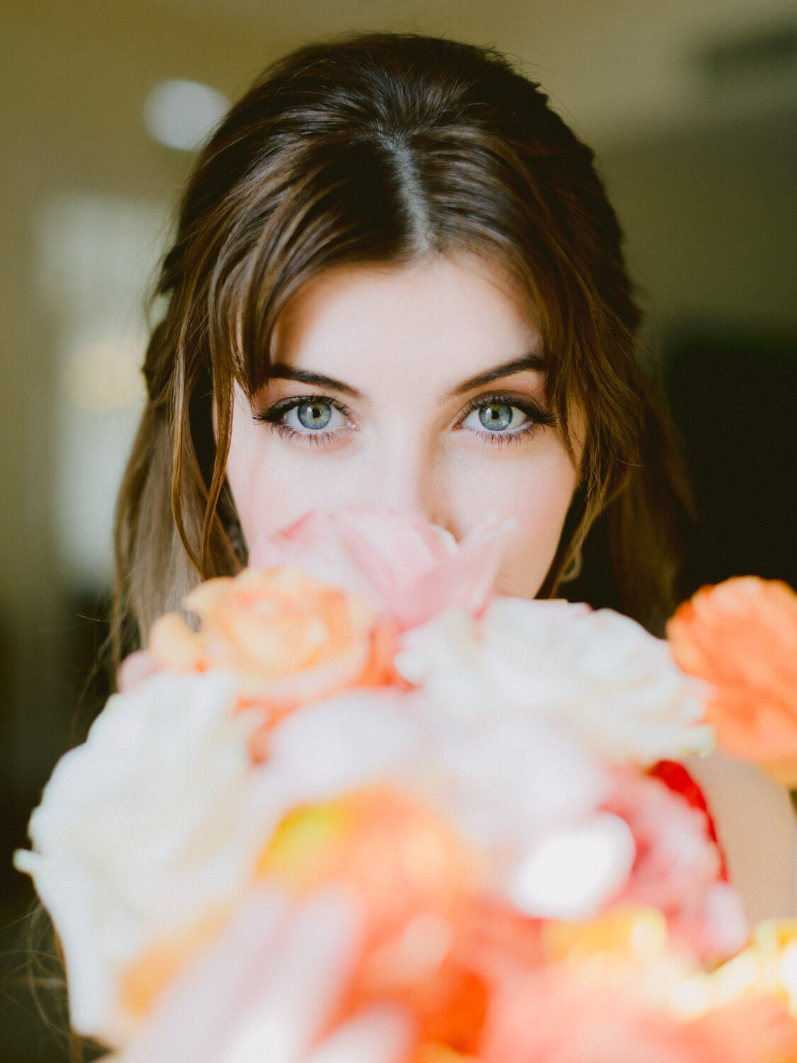 bride's eyes detail over out of focus colourful bouquet by Portugal Wedding Photographers