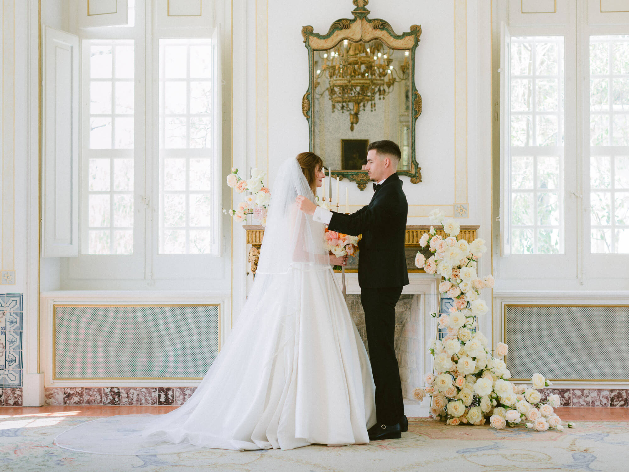 Bride and Groom in front of mantlepiece decorated with flowers in Palacio de Queluz by Portugal Wedding Photographers