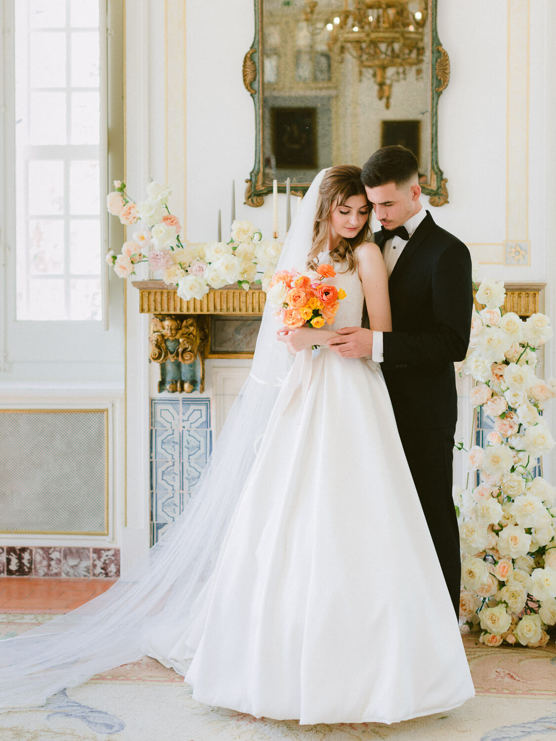 romantic bride and groom on wedding day posing in front of flower-decorated mantlepiece by Portugal Wedding Photographer