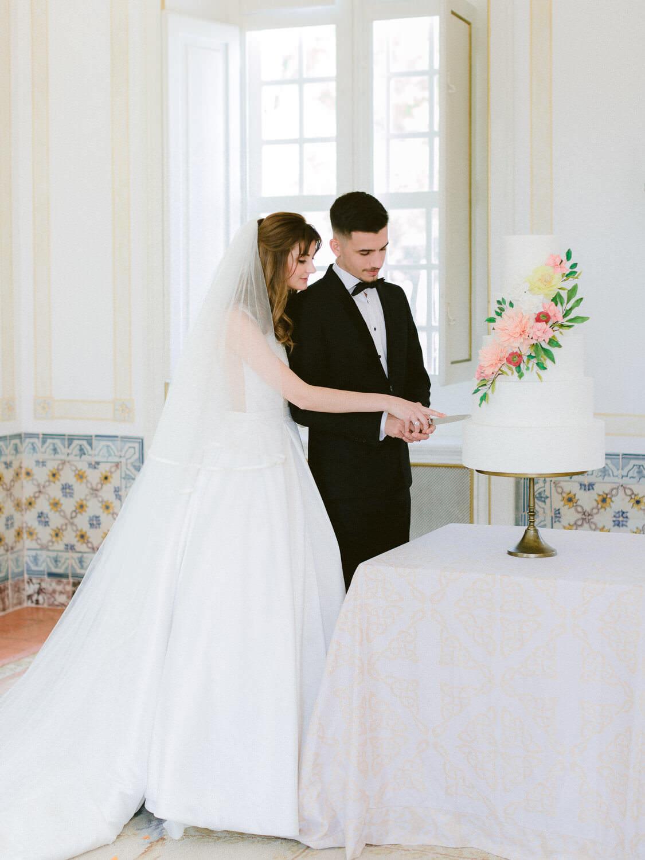 bride and groom cutting wedding cake at Palacio de Queluz by Portugal Wedding Photographer