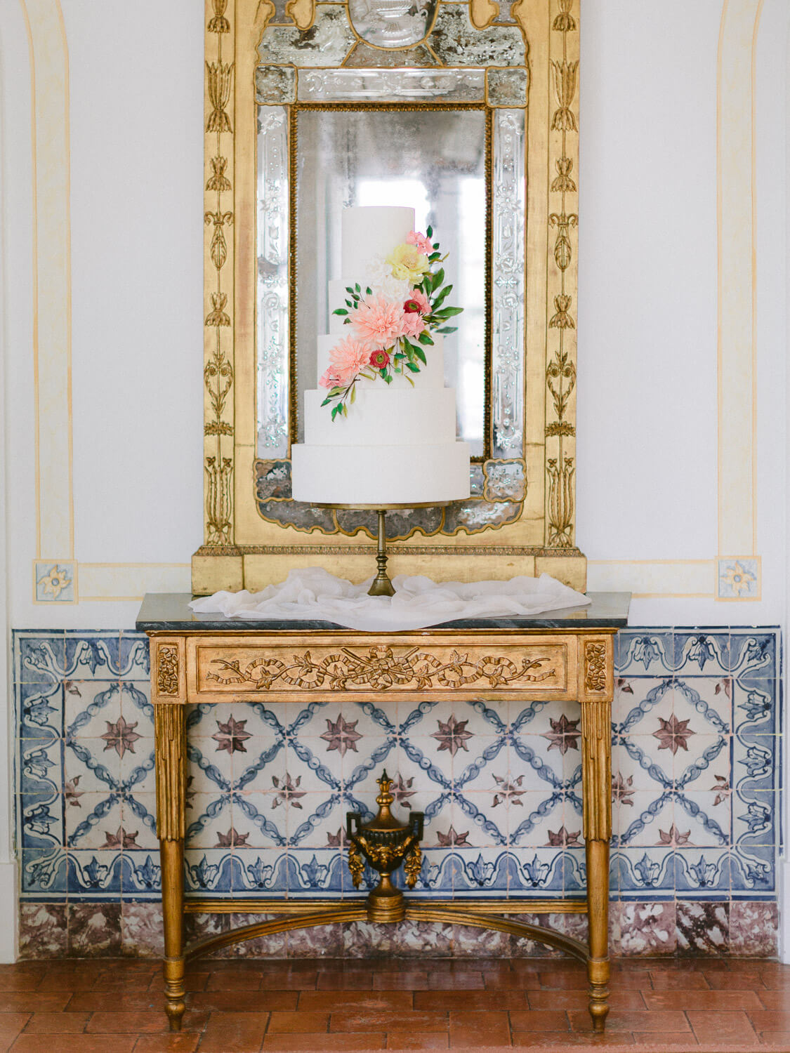 five-tiered, white wedding cake with flowers with Portuguese tiles backdrop by Portugal Wedding Photographer
