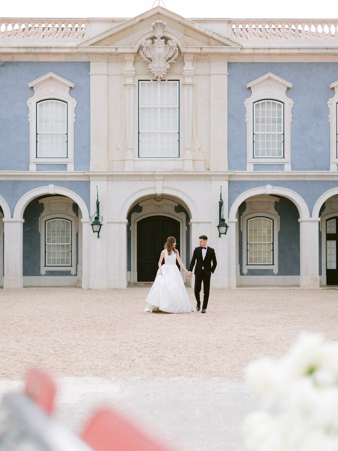 Gorgeous bride and groom portrait walking in front of beautiful Palacio de Queluz by Portugal Wedding Photographer