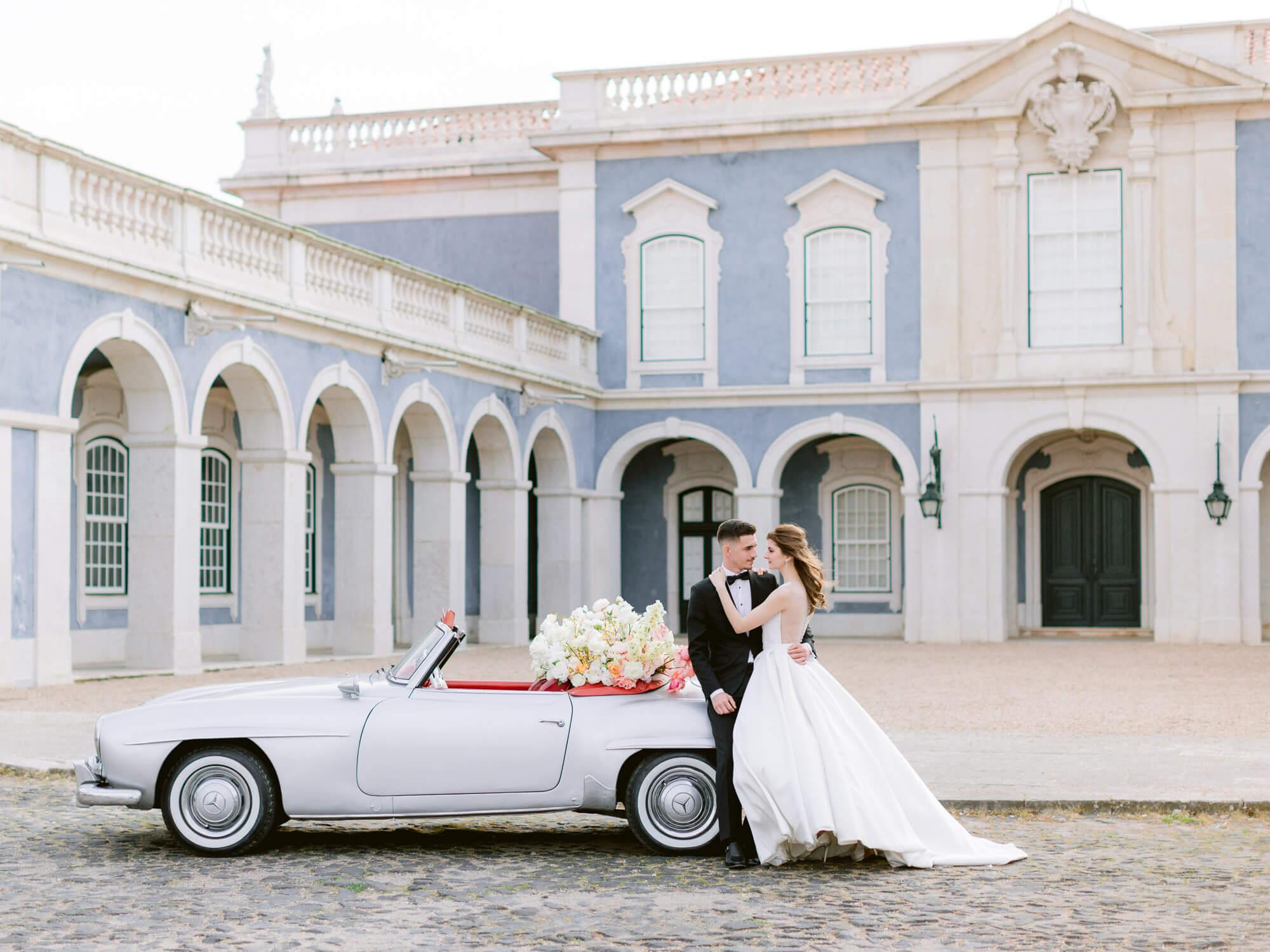 beautiful bride and groom, vintage car and Palacio de Queluz facade by Portugal Wedding Photographer