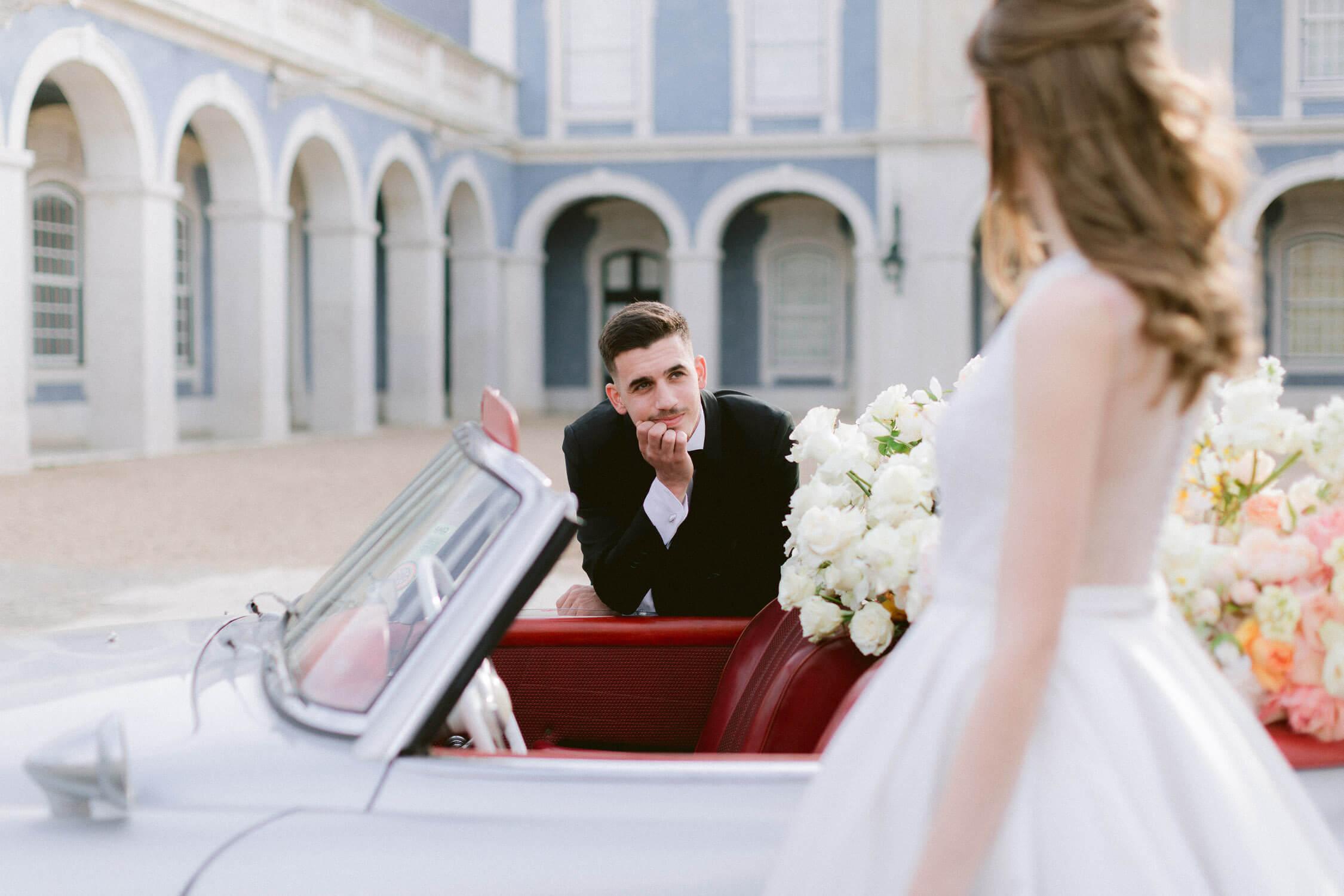 groom looking in awe of the bride in front of Palacio de Queluz by Portugal Wedding Photographer