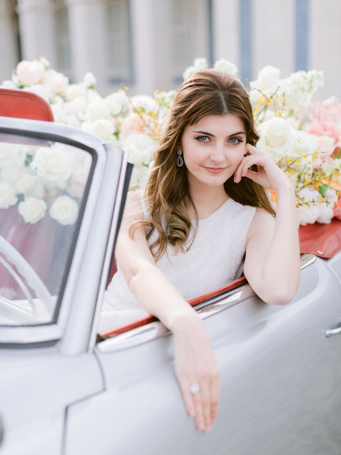 Beautiful bride's portrait in convertible car decorated with lots of white flowers