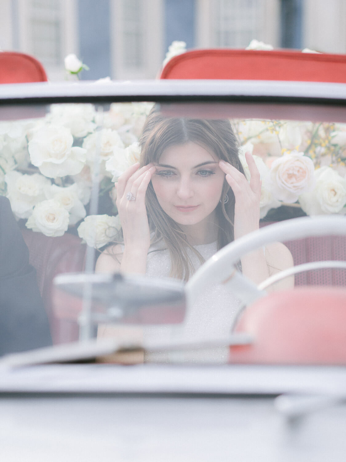 beautiful bride on the drives seat of a convertible decorated with white flowers by Portugal Wedding Photographer
