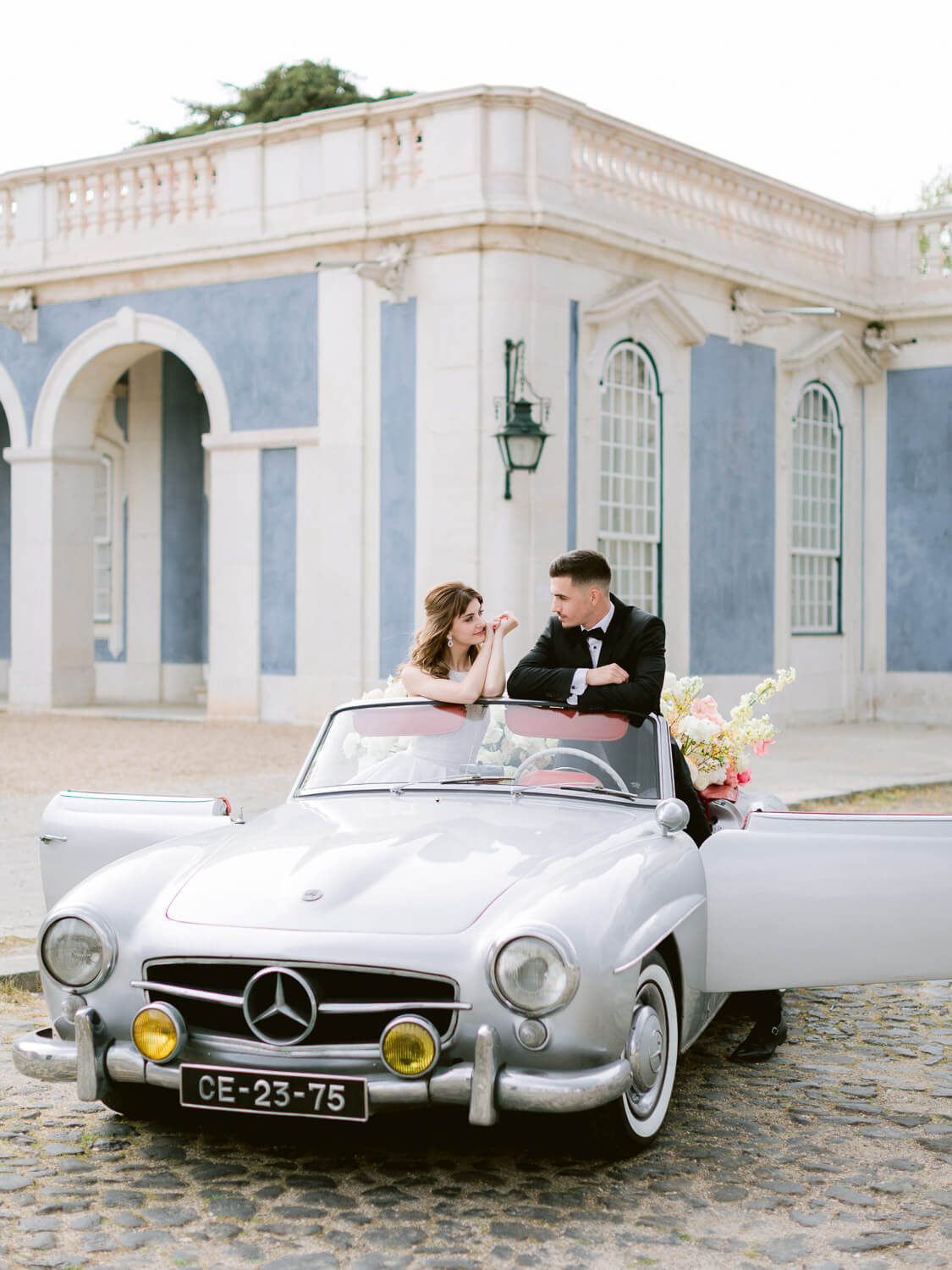 bride and groom posing on Mercedes Benz vintage convertible on wedding day by Portugal Wedding Photographer