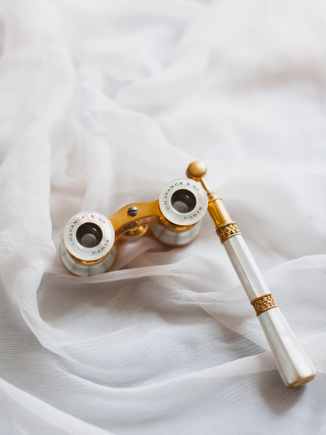 gold and mother of pearl detailed opera binoculars over silk draping photographed by Portugal Wedding Photographer