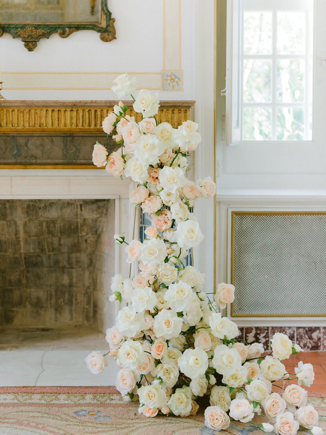 white and coral cascading floral decor on mantlepiece photographed by Portugal Wedding Photographer