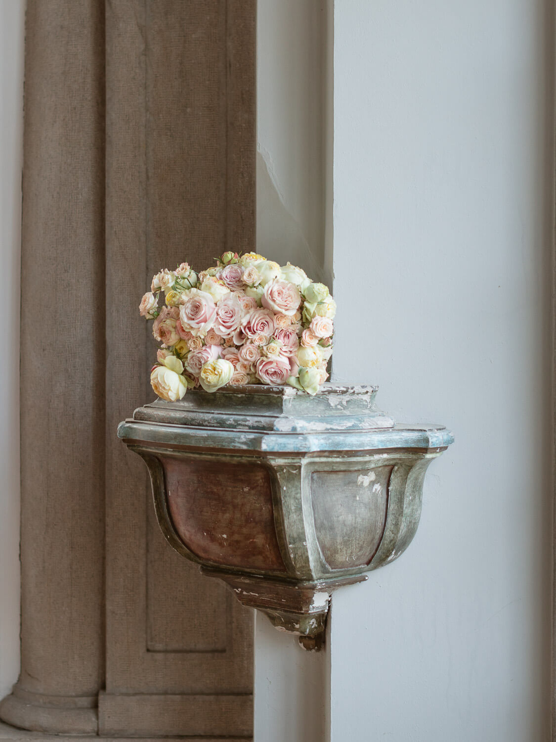 spray roses bridal bouquet over wall niche in Casa dos Penedos Sintra by Portugal Wedding Photographer