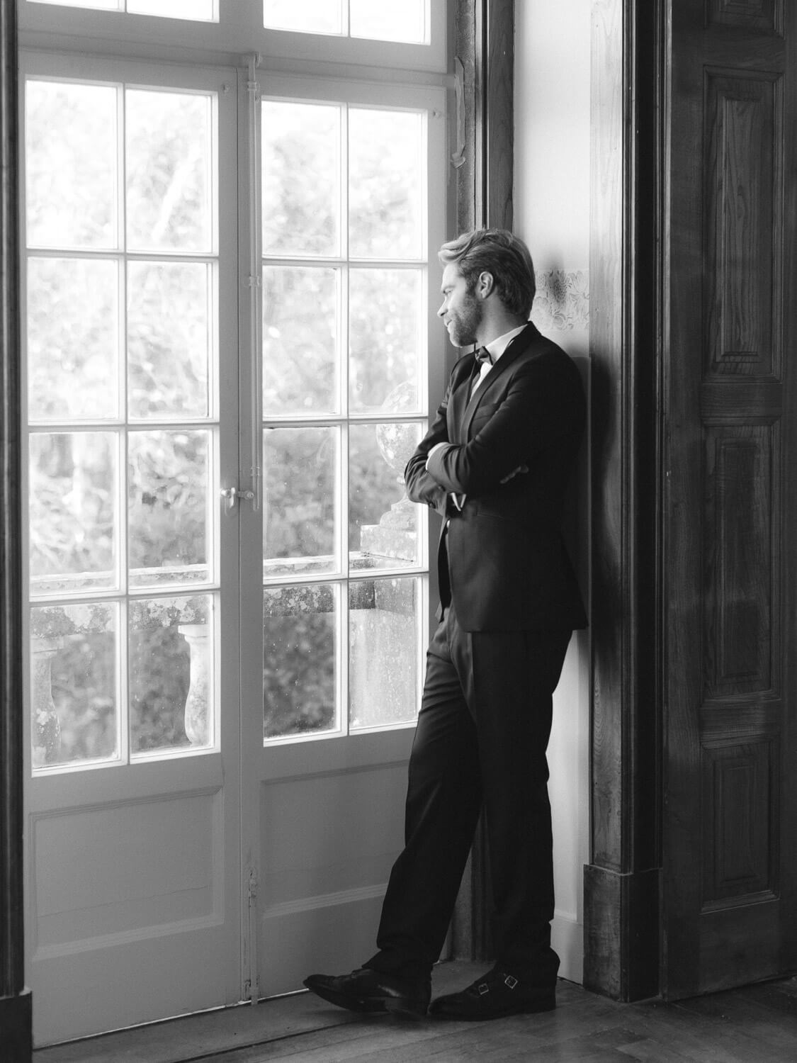 groom's romantic portrait by french door window in Casa dos Penedos Sintra by Portugal Wedding Photographer