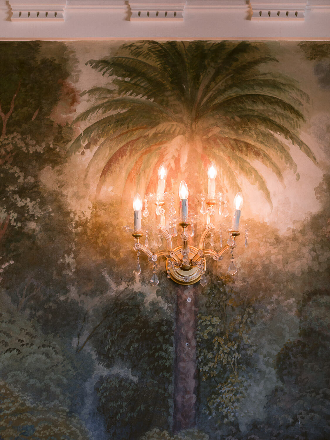 wall chandelier over vintage palm tree illustration on the wall in Casa dos Penedos Sintra by Portugal Wedding Photographer