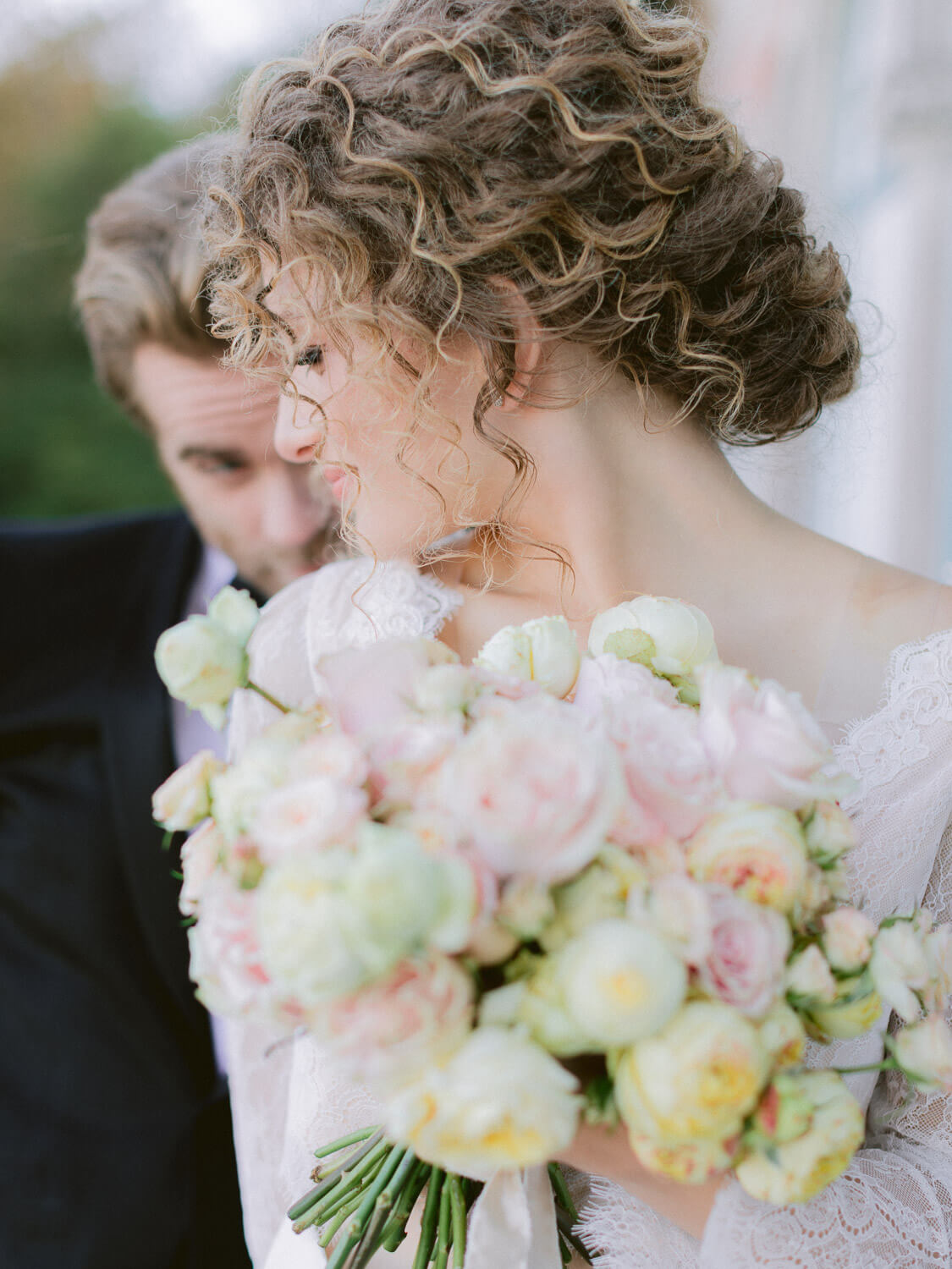 bridal bouquet out of focus with bride and groom in the background by Portugal Wedding Photographer