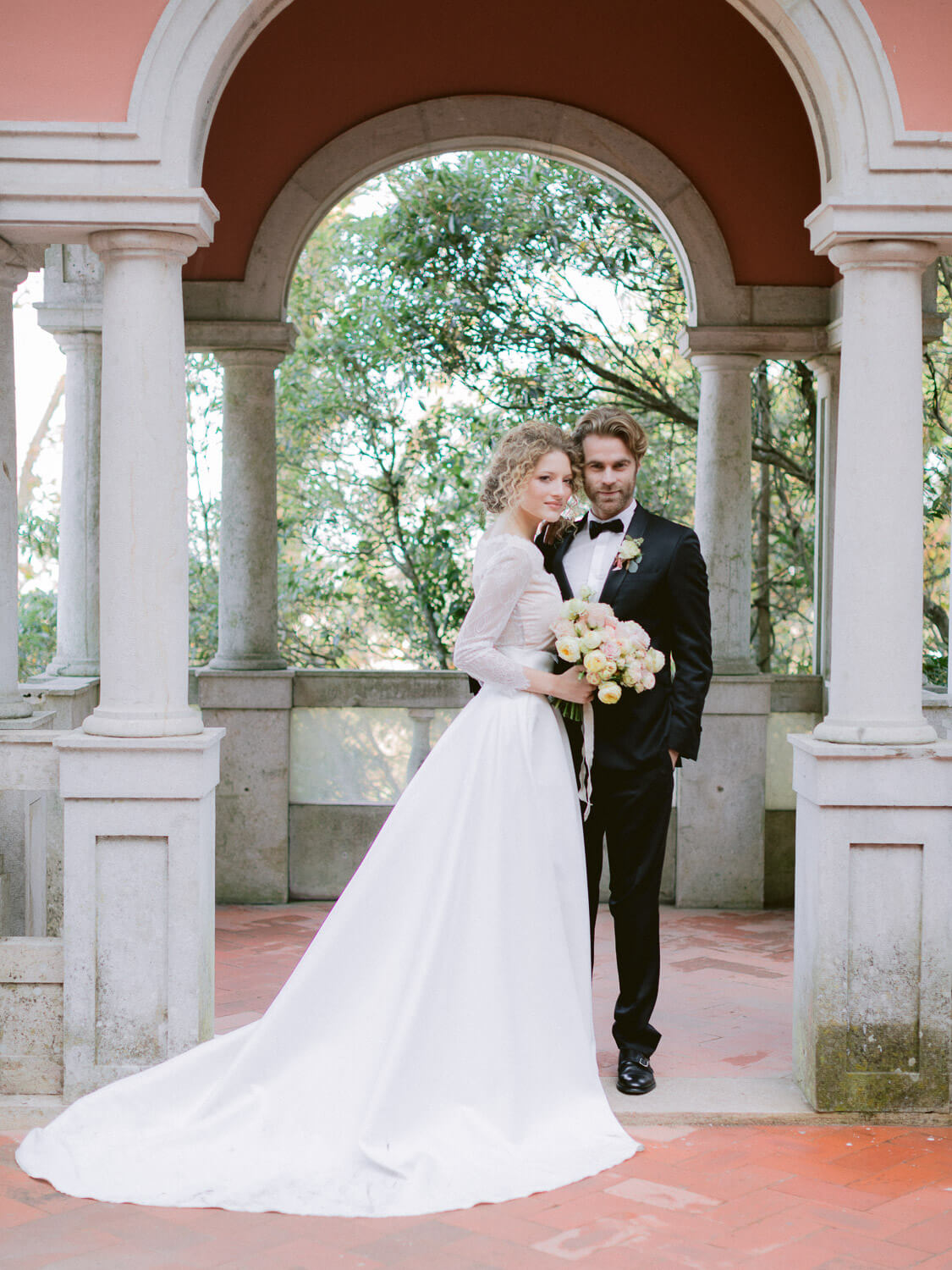 romantic bride and groom portrait framed by Casa dos Penedos arcades by Portugal Wedding Photographer
