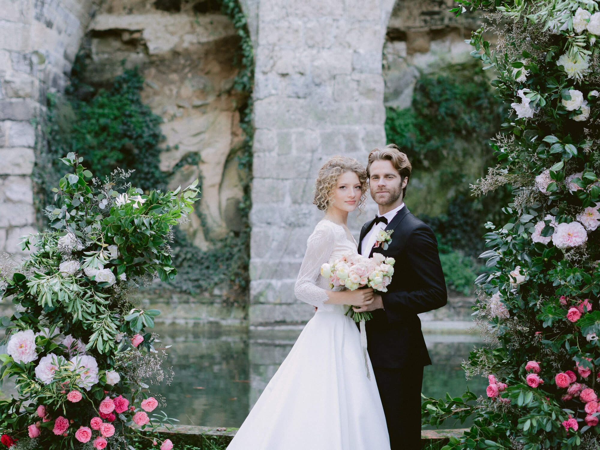 bride and groom's portrait in between ceremony arch by Portugal Wedding Photographer