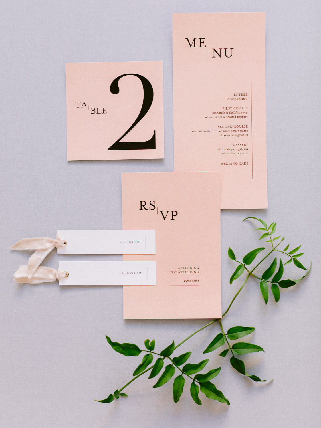 flat-lay with salmon wedding stationery and greenery by Portugal Wedding Photographer