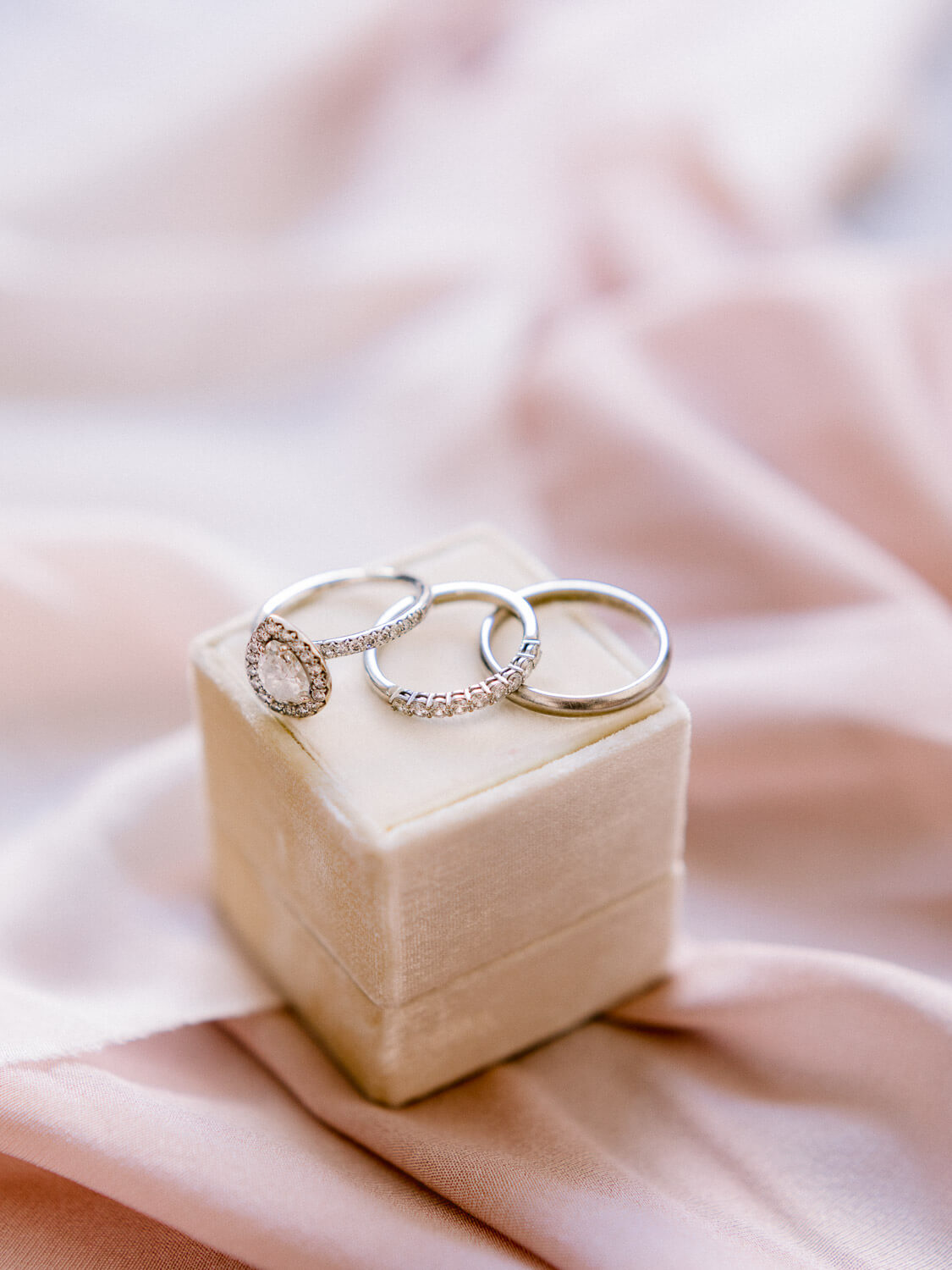 wedding bands, engagement ring and beige velvet ring box detail by Portugal Wedding Photographer