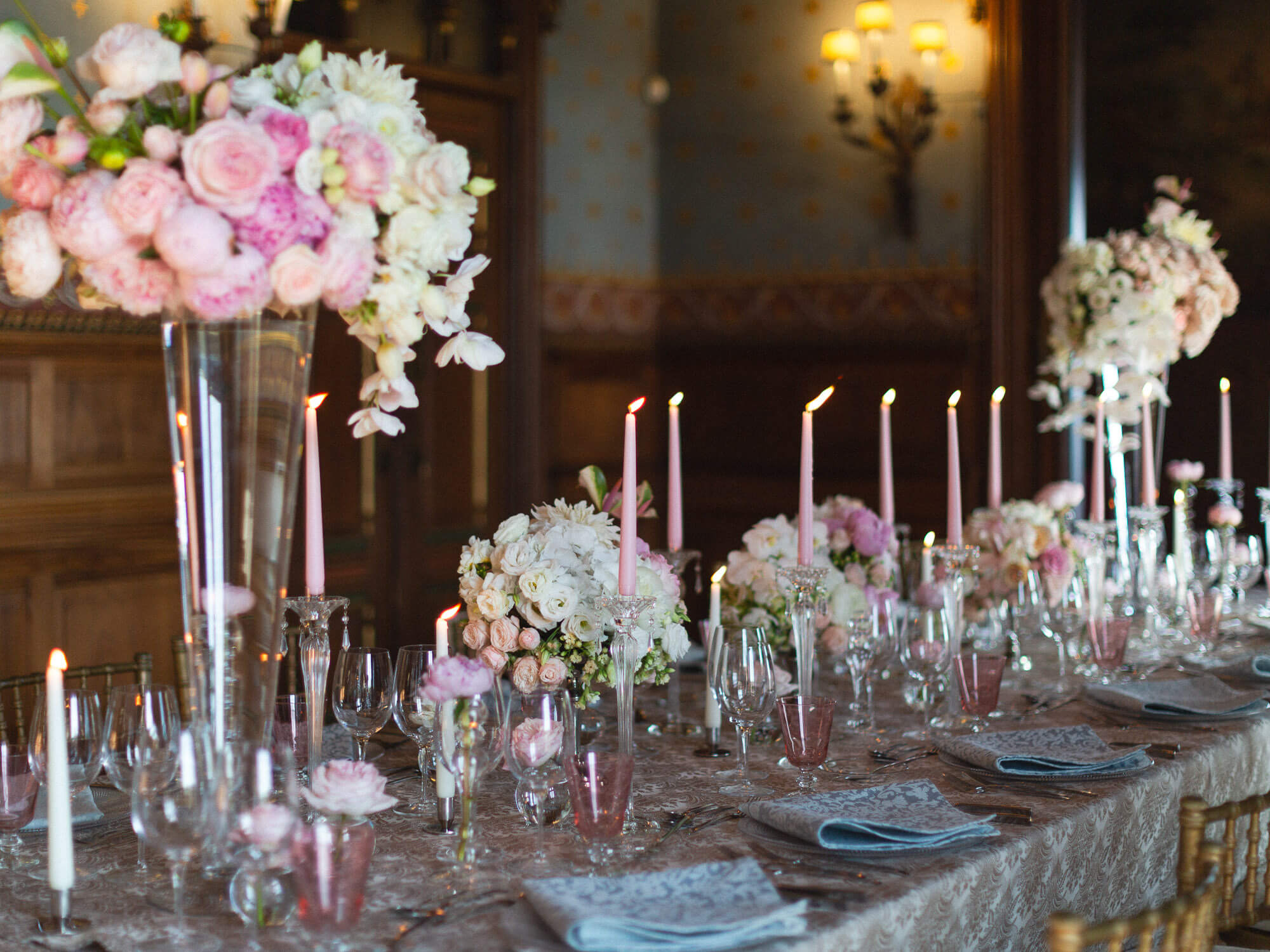 wedding reception hall with tables decorated with lush pink florals by Portugal Wedding Photographer