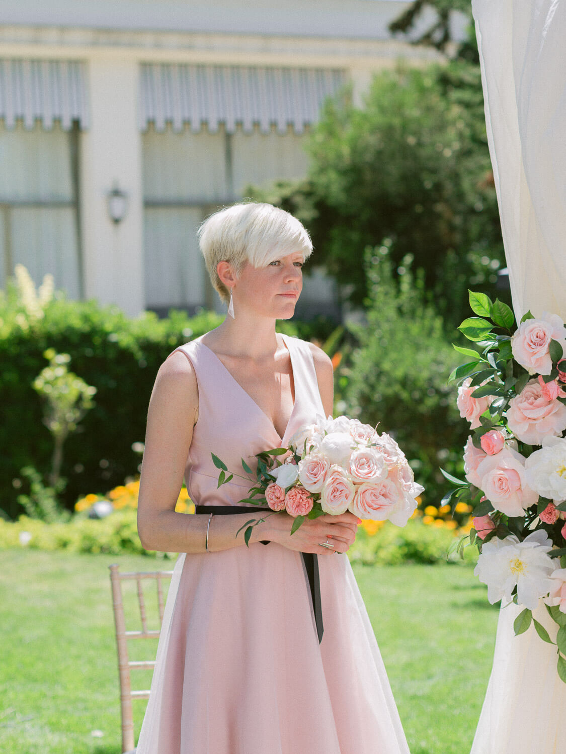 maid-of-honour holding bridal bouquet during a wedding ceremony in Hotel Palacio Estoril by Portugal Wedding Photographer
