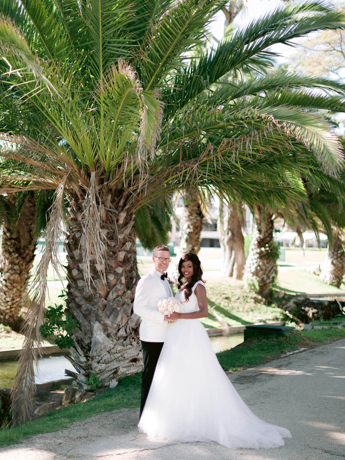 newlyweds under a palm tree after the wedding ceremony at Hotel Palacio Estoril by Portugal Wedding Photographer