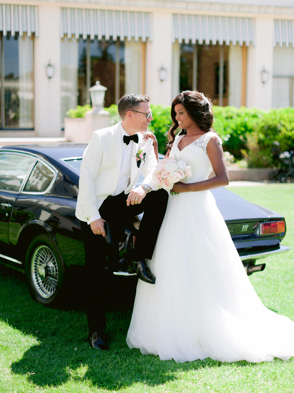 bride and groom and a vintage black car in Palacio Hotel Palacio Estoril's gardens by Portugal Wedding Photographer