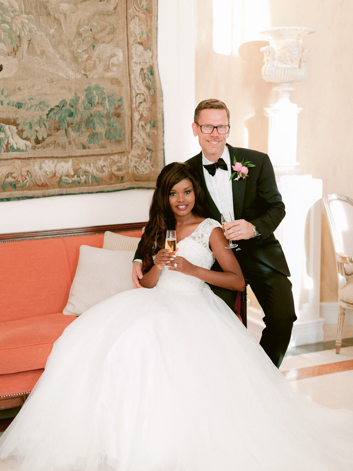 charming wedding couple on an elegant crimson couch in Hotel Palacio Estoril by Portugal Wedding Photographer