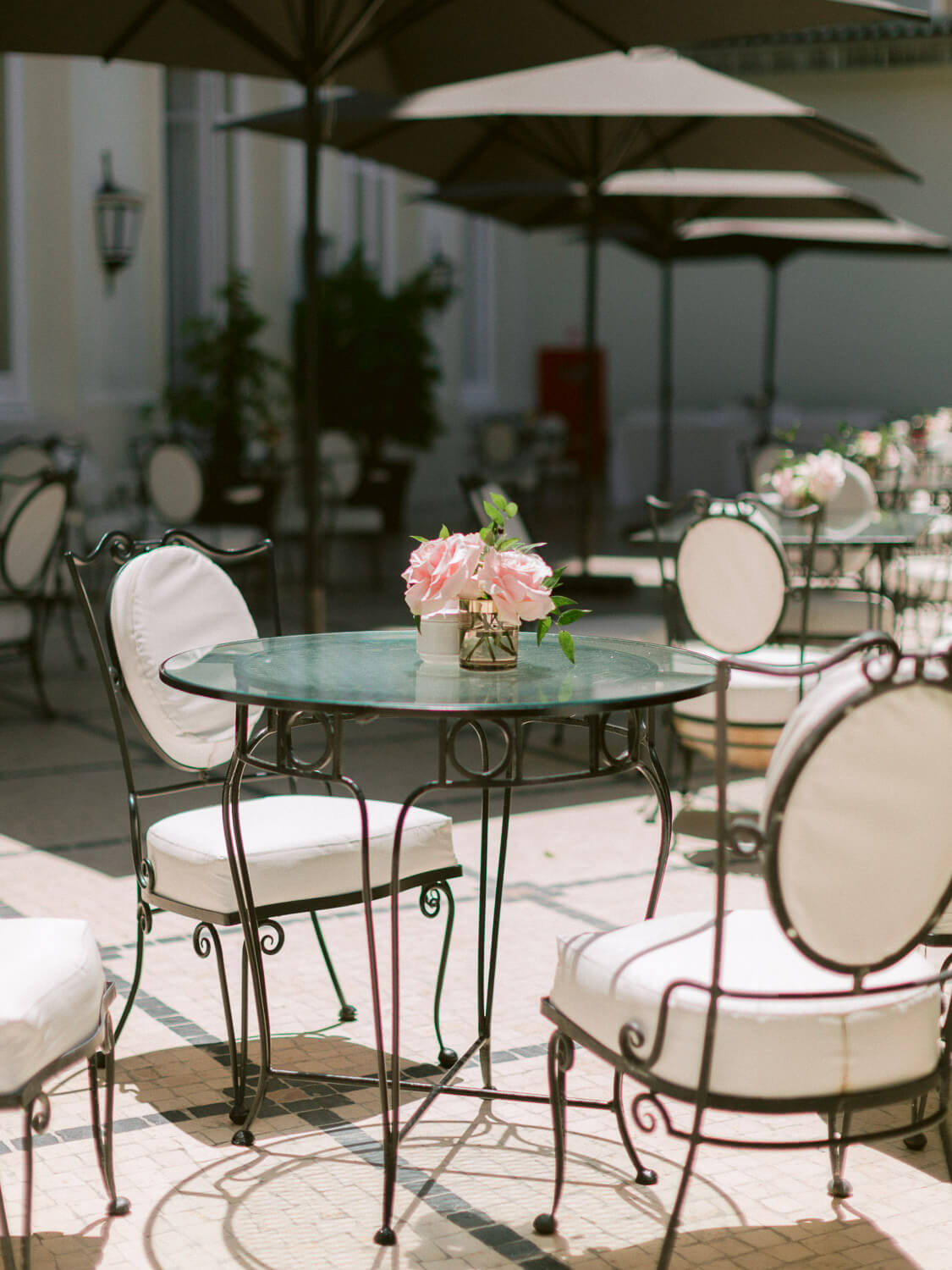 chic garden tables with roses centrepieces for wedding cocktail in Hotel Palacio Estoril by Portugal Wedding Photographer