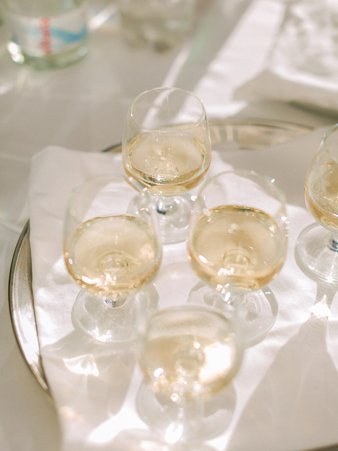 white wine glasses close up during wedding cocktail by Portugal Wedding Photographer