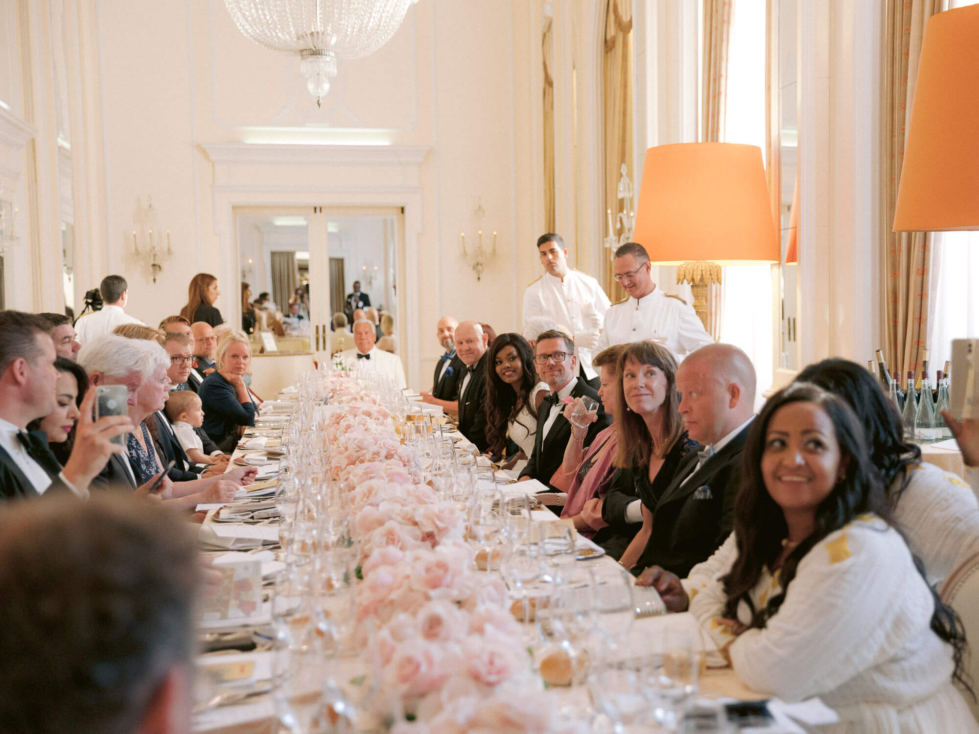 wedding guests enjoying dinner on a long table by Portugal Wedding Photographer