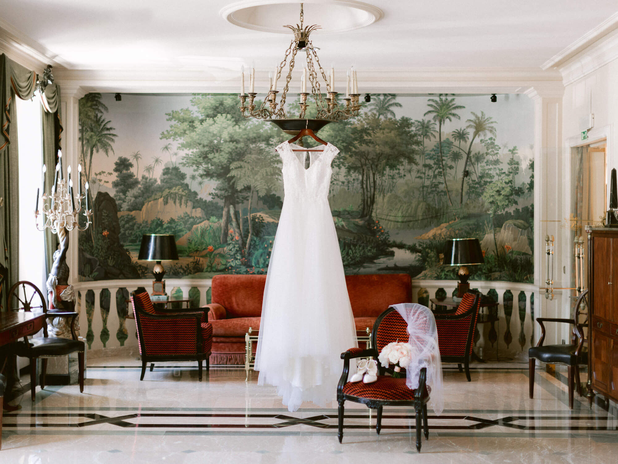 bride's dress hanged on chandelier in Hotel Palacio Estoril by Portugal Wedding Photographer