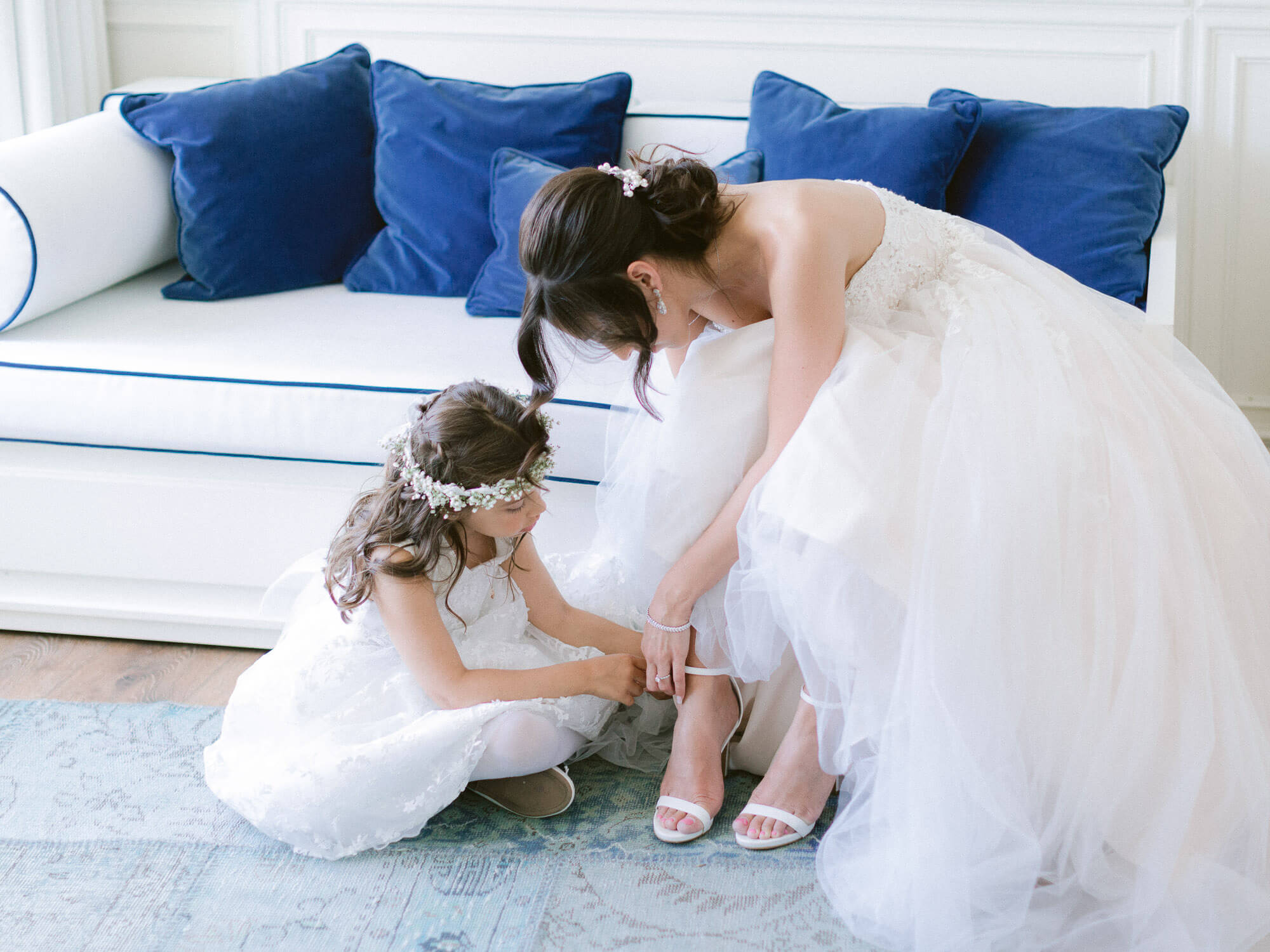 flower girl helping bride with her white sandals