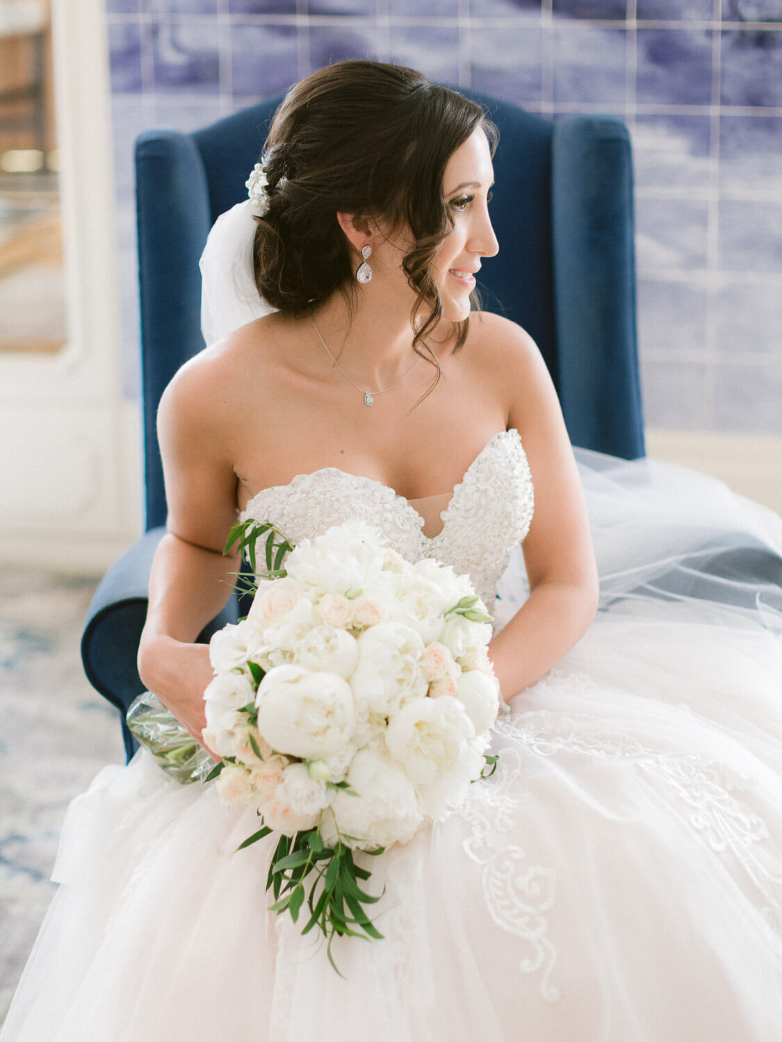 bridal sitting down portrait with white florals bouquet by Portugal Wedding Photographer