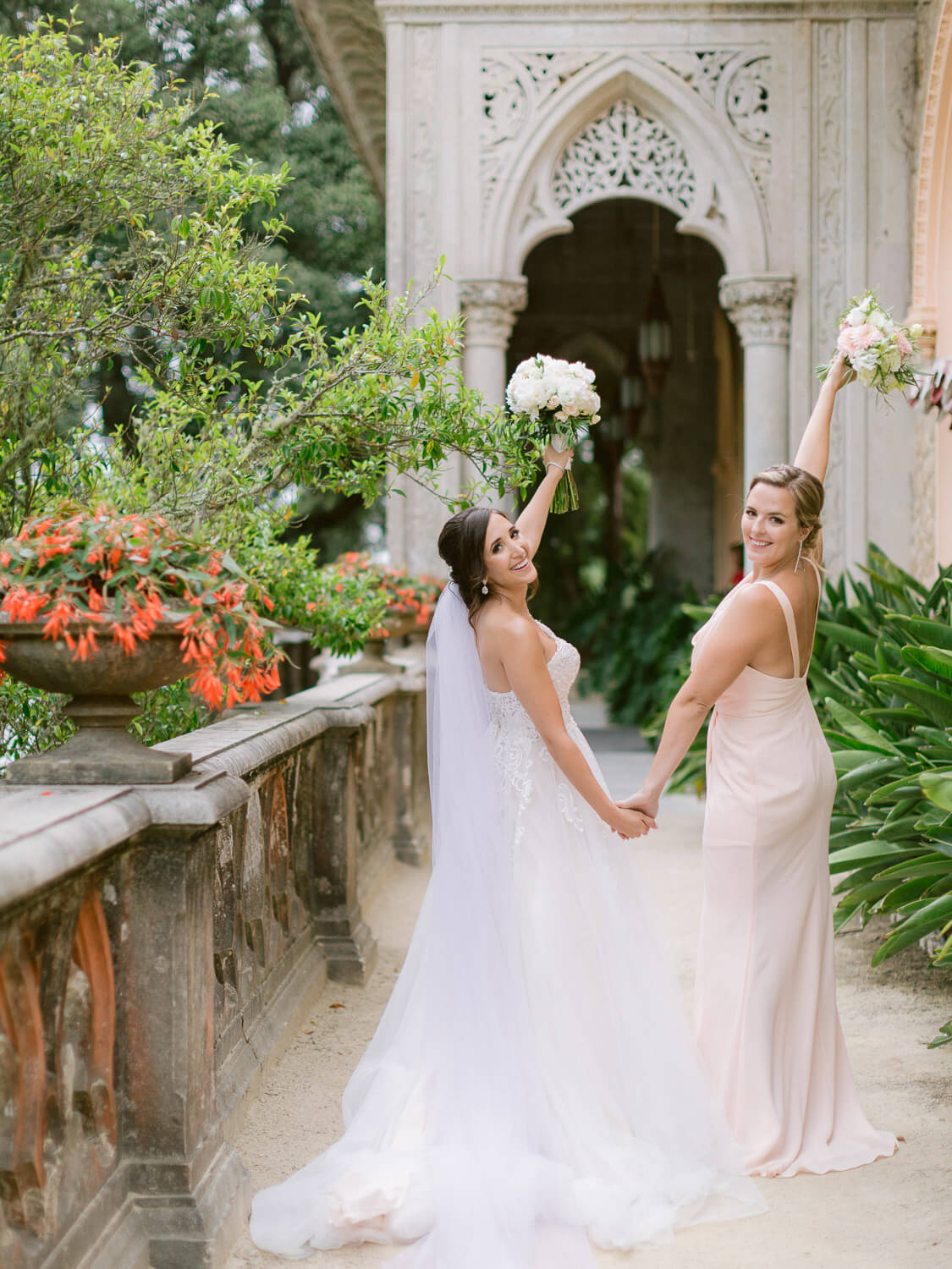 Bride and Maid-of-honour cheering with floral bouquets in Monserrate Palace Wedding by Portugal Wedding Photographer