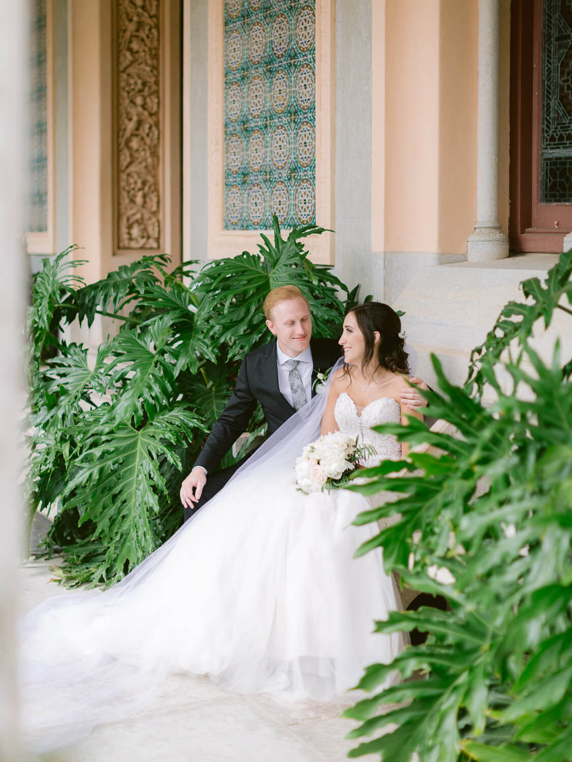 sweet newlyweds sitting in between large plants over Monserrate Palace decorated facade by Portugal Wedding Photographer